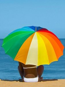 BDDDCE An attractive young African woman holding a multi coloured umbrella sitting on a sandy beach with a blue sea in the background.. Image shot 07/2009. Exact date unknown.